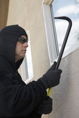Burglar using crowbar to break into house Stock Photo - 3540785