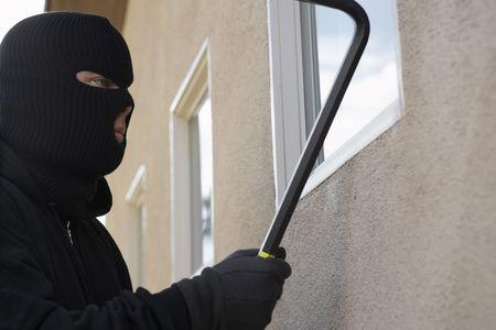 Burglar using crowbar to break into house Stock Photo - 3540719