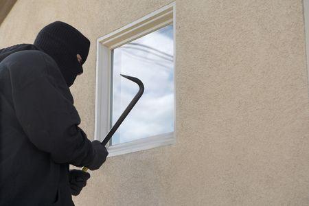 Burglar using crowbar to break into house Stock Photo - 3540921