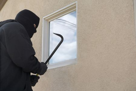 Burglar using crowbar to break into house Stock Photo