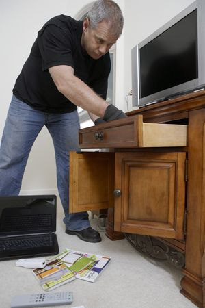Burglar looking through drawers in  Stock Photo