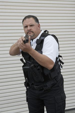 Portrait of security guard in bulletproof vest holding gun Stock Photo - 3540792
