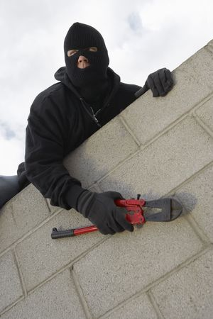 burglar protection: Masked thief climbing wall
