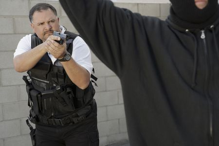 Security guard aiming gun at thief Stock Photo - 3540848