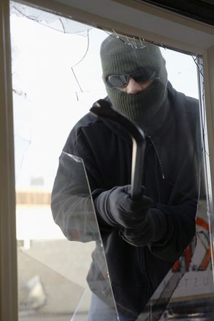 Masked thief braking glass with crowbar Stock Photo - 3540795