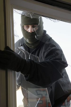 obscured: Masked thief braking in through window