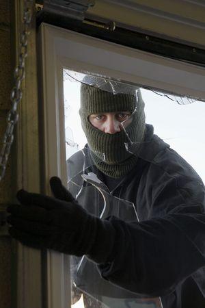 window opening: Masked thief braking in through window