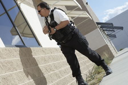 security vest: Security guard with gun patrolling