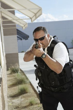 Security guard aiming with gun outdoors Stock Photo - 3540746