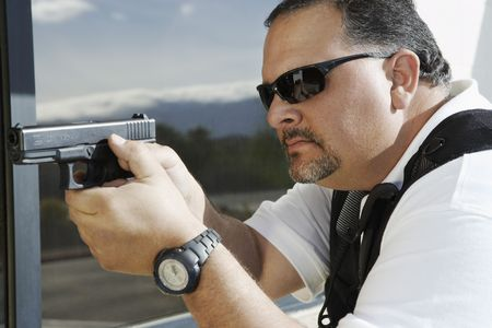 Security guard aiming with gun outdoors Stock Photo - 3540810