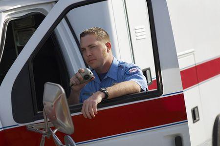 cb: Paramiedic using CB radio, leaning on ambulance LANG_EVOIMAGES