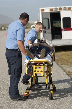 emergency stretcher: Paramedics transporting victim on stretcher
