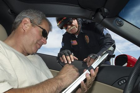 traffic ticket: Police officer watching driver signing papers, view from car