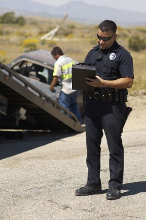 one person with others: Police officer writing notes, tow truck driver lifting crashed car in background LANG_EVOIMAGES