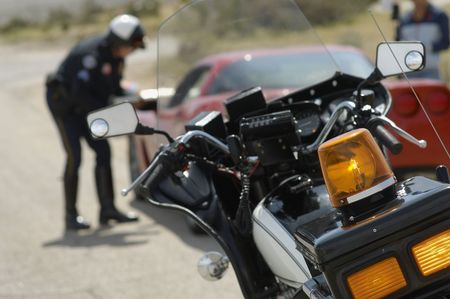 traffic cop: Traffic cop talking with car driver, focus on motorcycle in foreground