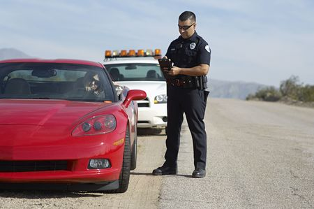 Traffic cop standing by sports car LANG_EVOIMAGES