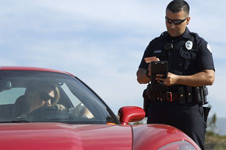 Traffic cop standing by sports car Stock Photo