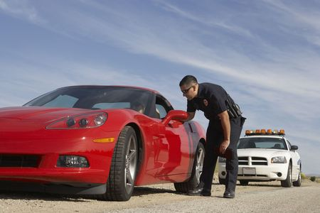 Traffic cop talking with driver of red sports car Stock Photo - 3540796