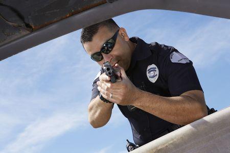 window shades: Police officer aiming gun through car window