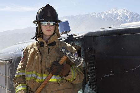 Portrait of female firefighter holding axe in mountains Stock Photo - 3540856
