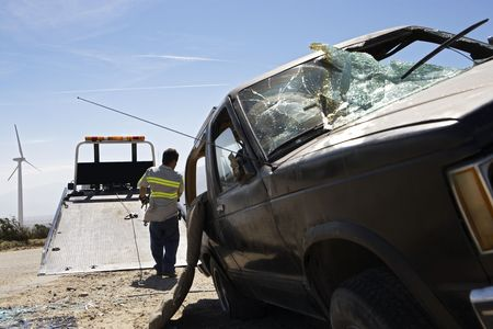 crashed: Man preparing to lift crashed car onto tow truck