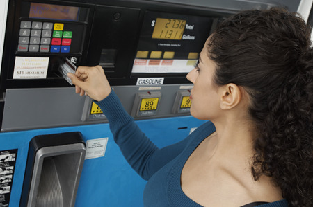 Woman paying with credit card at gas pump Stock Photo - 3812386