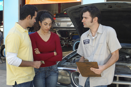 Couple talking to mechanic in front of open car hood Stock Photo - 3812525