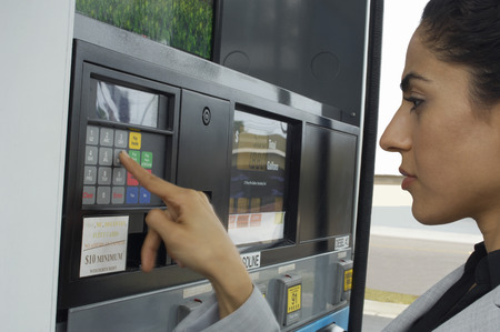 Woman pushing buttons on gas pump Stock Photo - 3812225