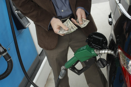 Man counting money over gas pump in car, mid section Stock Photo - 3812542