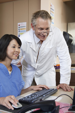 Nurse and doctor working on computer