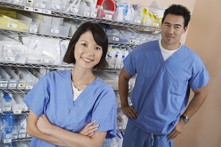 Female and male nurse standing by shelves with medical supply, portrait Stock Photo - 3812370