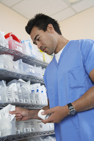 asian nurse: Male nurse standing by shelves with medical supply, low angle view LANG_EVOIMAGES