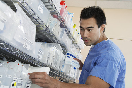 Male nurse standing by shelves with medical supply, low angle view Stock Photo - 3812352