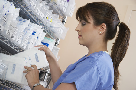 pharmacist: Female nurse standing at shelf with medicinal supplies