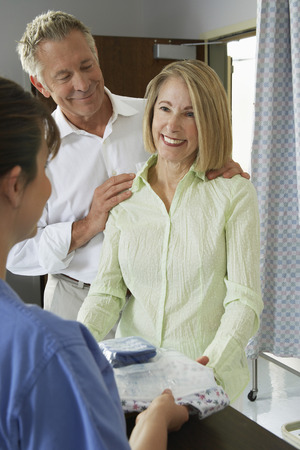 Nurse giving examination gown to female patient Stock Photo - 3812283