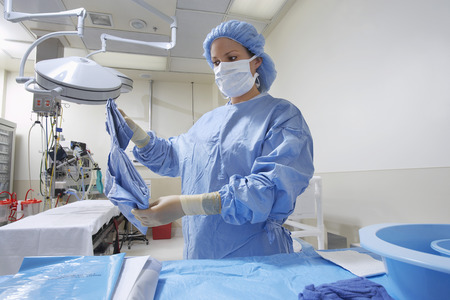 hospital gown: Nurse preparing bed in operating room
