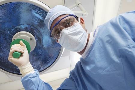 Surgeon adjusting lamp, low angle view Stock Photo - 3812359