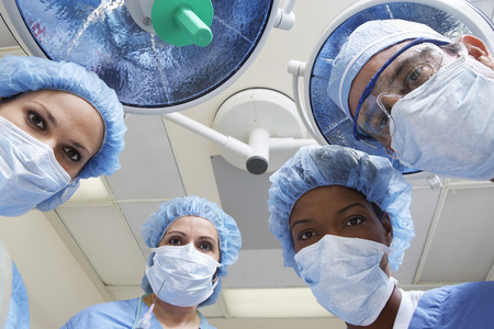 hospital gown: Four surgeons looking down, low angle view