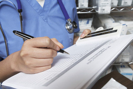 Female doctor writing in patient chart, mid section Stock Photo - 3811144