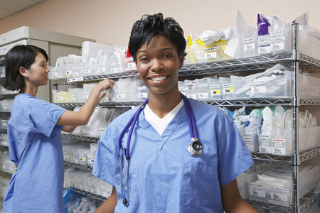 Portrait of female doctor, nurse standing by shelves with medical supplies in background Stock Photo
