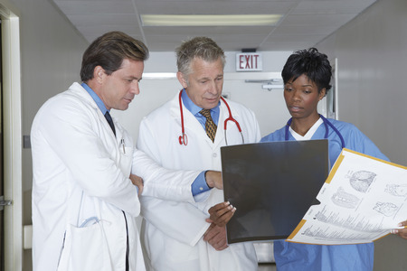 Medical personnel looking at x-ray image in hospital hallway Stock Photo - 3811155