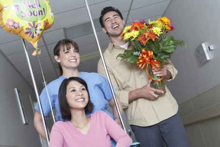 going: Nurse and man with bouquet assigning woman on wheelchair in hospital hallway