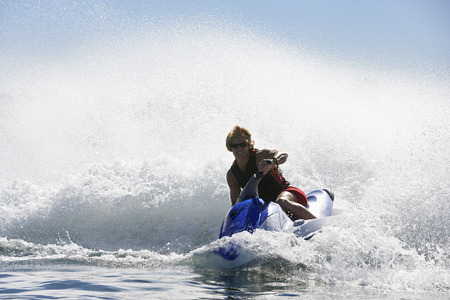 jetski: Young man riding jetski on lake