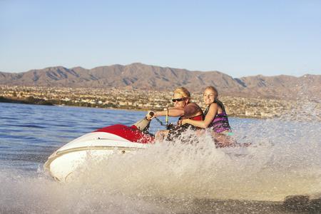 Young couple riding jetski on lake Stock Photo - 3812539