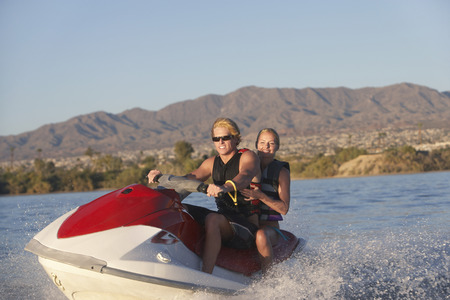 Young couple riding jetski on lake Stock Photo - 3811204