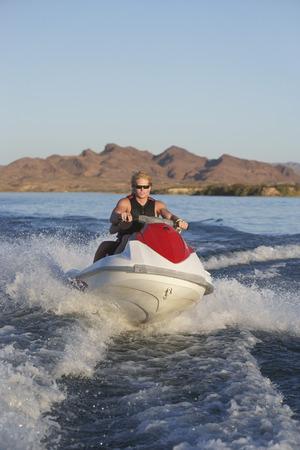 Young man riding jetski on lake Stock Photo - 3812233