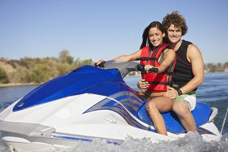 jetski: Young couple riding jetski on lake, portrait LANG_EVOIMAGES