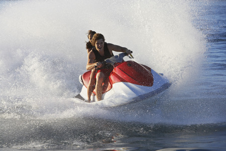 jetski: Young couple riding jetski on lake LANG_EVOIMAGES