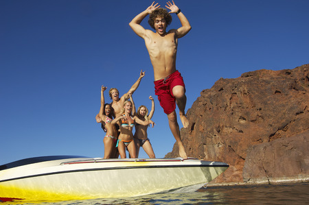 small boat: Young man jumping from boat, friends watching in background LANG_EVOIMAGES