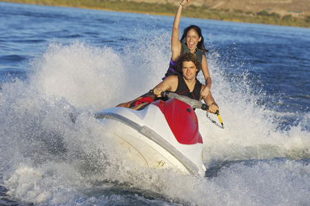 Young couple riding jetski on lake Stock Photo - 3812584